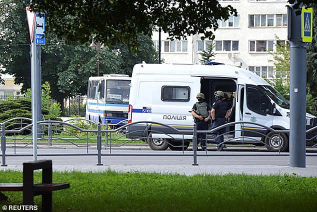 Armed officers stand in front of a police van.  The bus where the hostages are held can be seen behind