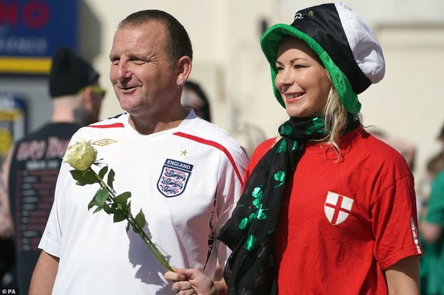 A man and woman wearing England shirts stand on the street as they wait for the funeral cortege of Jack Charlton today