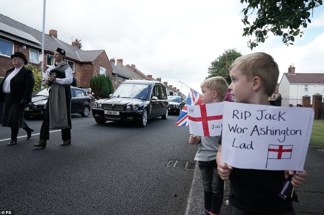 Two boys hold up signs paying tribute to Jack Charlton as the funeral cortege passes through Ashington this morning