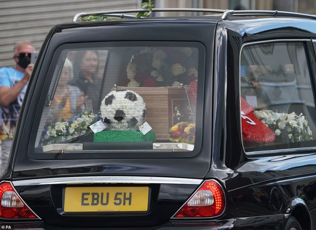 A football-themed tribute to Jack Charlton is seen through the window as the funeral cortege passes through this morning