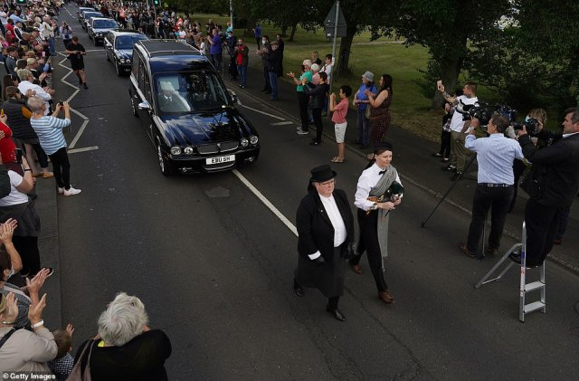 Mourners applaud as Jack Charlton's funeral cortege passes through his childhood hometown of Ashington this morning