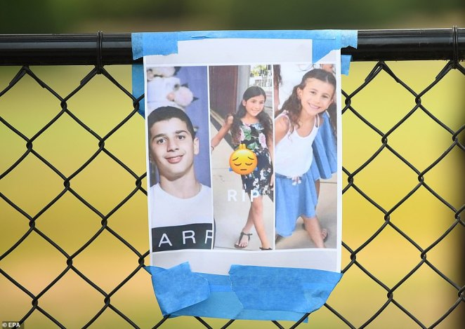 A photo of the victims hangs from a fence at the scene where seven children were hit by a four-wheel drive (4WD) in the suburb of Oatlands in Sydney