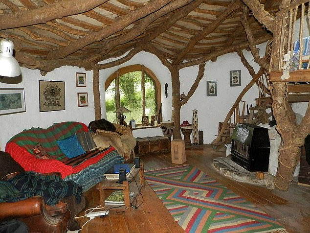 Pictured: The cosy living area, which is heated by a woodburner. The property also generates its own electricity