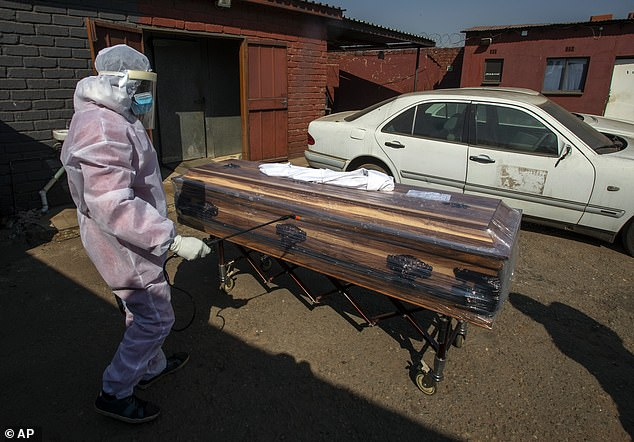 A funeral home worker in protective gear disinfects a casket carrying a woman who died of COVID-19, as they prepare for a funeral in Katlehong, near Johannesburg, South Africa, yesterday.