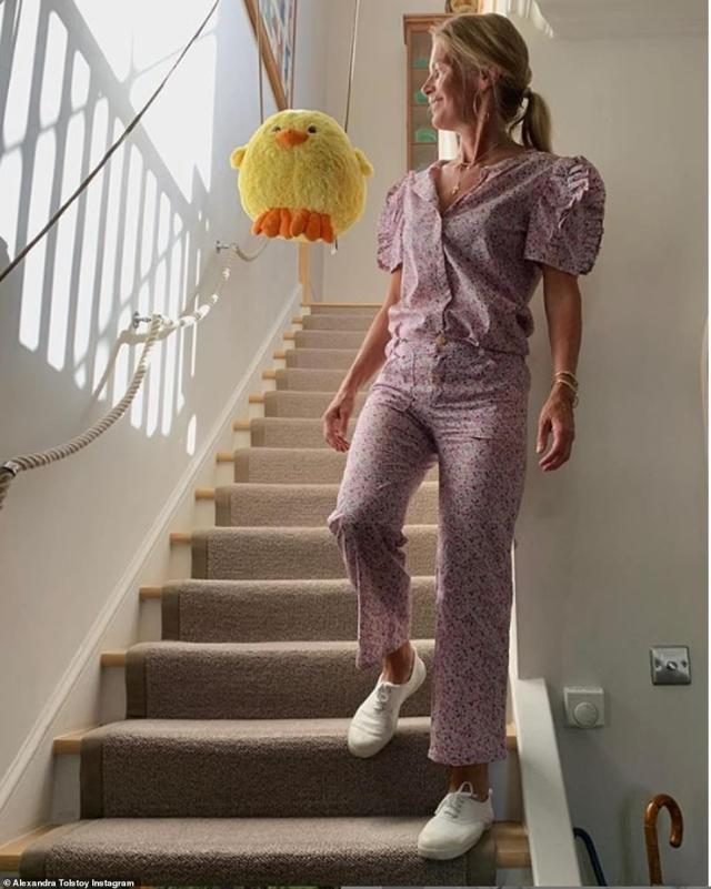 Alexandra poses on the stairs of her multi-storey former home which comes complete with a sweet children's rope banister