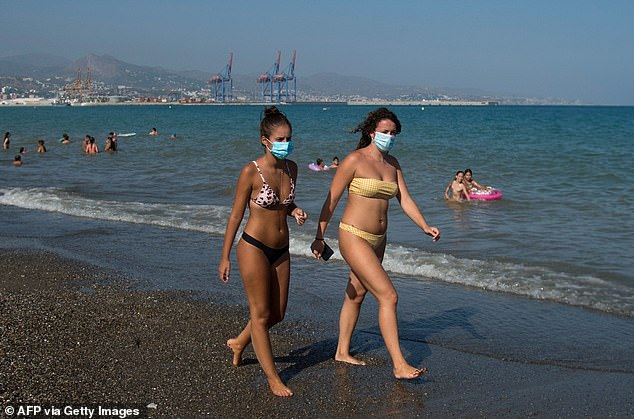 People wearing face masks walk along La Misericordia Beach, Malaga, earlier this week as Spain faces a fresh blow to its tourism industry due to coronavirus