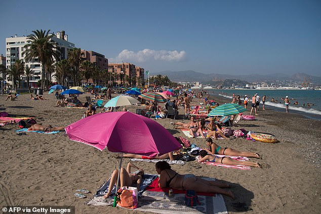 People sunbathing at the La Misericordia Beach, Malaga, this week amid fears that the Spanish tourism industry will collapse