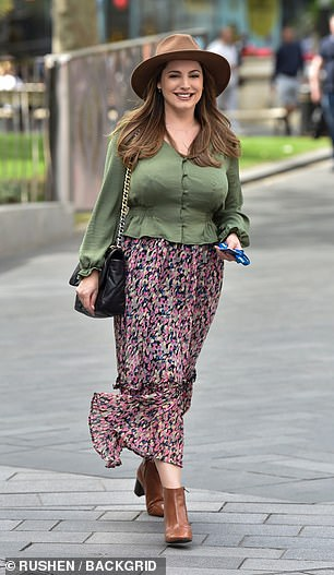 Mixing up her usual look: She wore a green silky blouse which clinched Kelly's waist