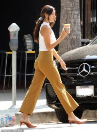 Eiza Gonzalez showcases her figure in high waist pants and a tight white top while getting a coffee