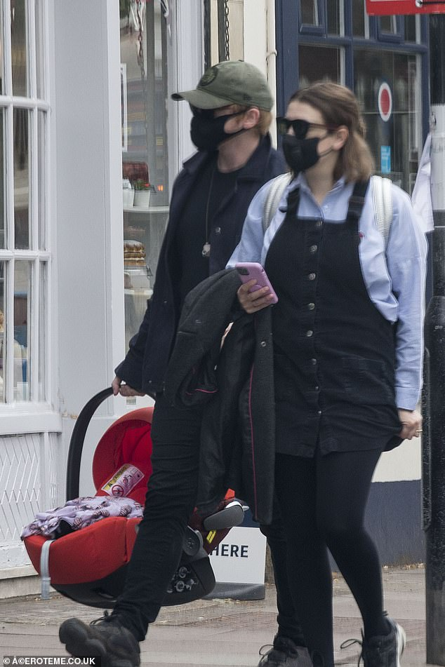Outing: Rupert Grint donned a mask as he stepped out with girlfriend Georgia Groome and their two-month-old daughter for a stroll through London on Tuesday