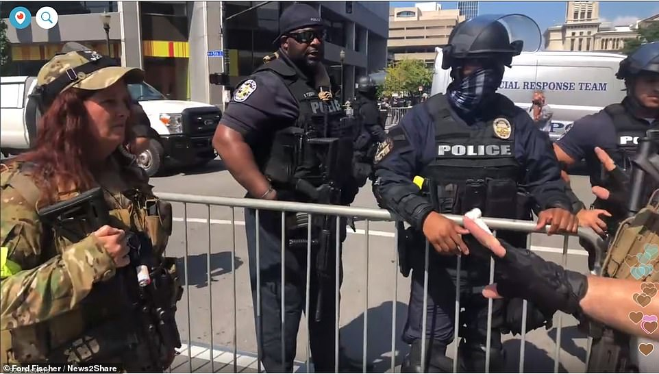 Louisville police officers are seen forming a barricade to separate the Three Percenters militia members from Black Lives Matter sympathizers on Saturday