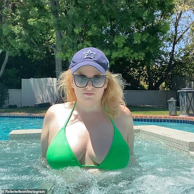 Rebel Wilson flaunts her cleavage in a neon green bikini while relaxing in a hot tub