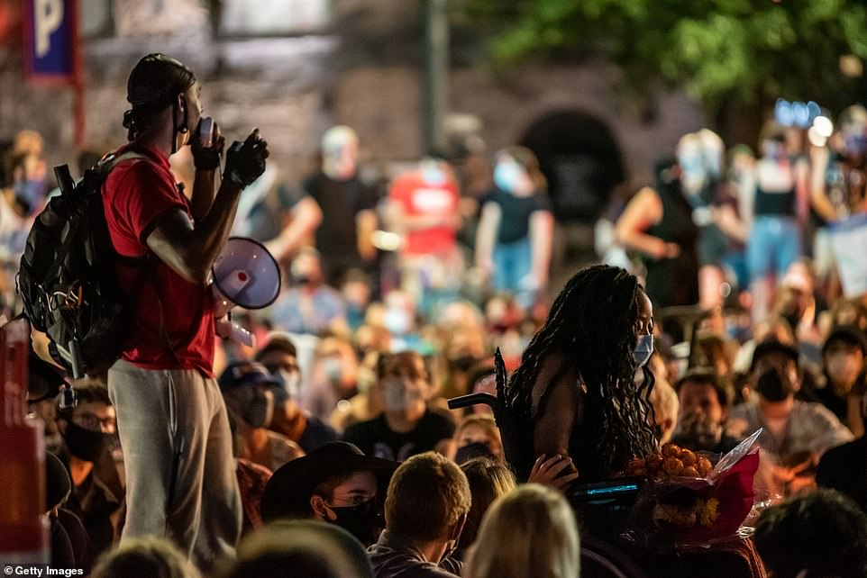 Activists including Whitney Mitchell, the wheelchair-bound fiancee of Garrett Foster, take part in a sit-in demonstration in downtown Austin on Sunday night