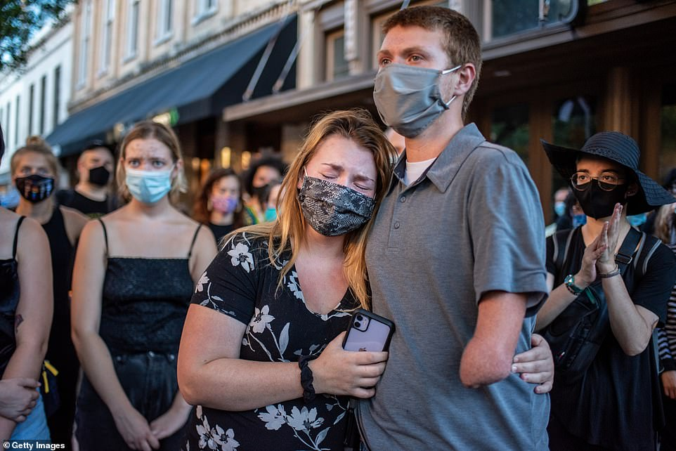 Other members of the crowd embraced and some broke down in tears as protesters chanted 'say his name, Garrett Foster' during the Sunday-night vigil