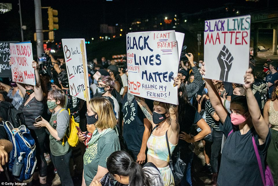 People hold up signs outside Austin Police Department after a vigil for Garrett Foster on July 26, 2020 in downtown Austin