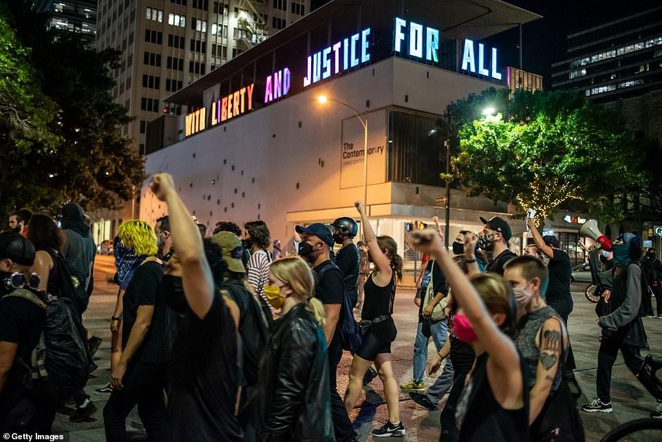 Protesters walk down 7th street in Austin after a vigil for Garrett Foster