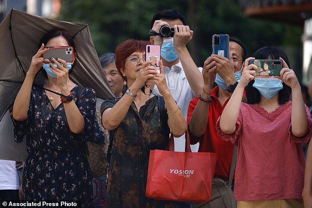 Residents are seen taking photos and video as Chinese authorities prepare to enter the United States Consulate in Chengdu in southwest China's Sichuan province on Monday, July 27