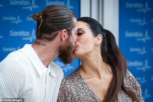 Kiss: The couple showered each other with affection outside Madrid's La Moraleja Hospital