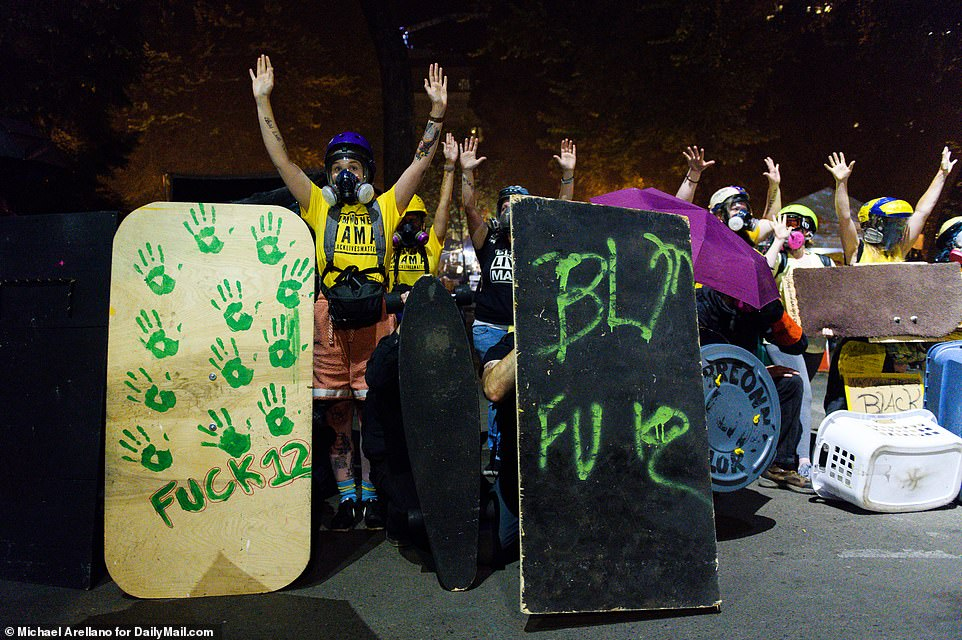Several moms stand behind protesters holding shields during another night of protests in downtown Portland