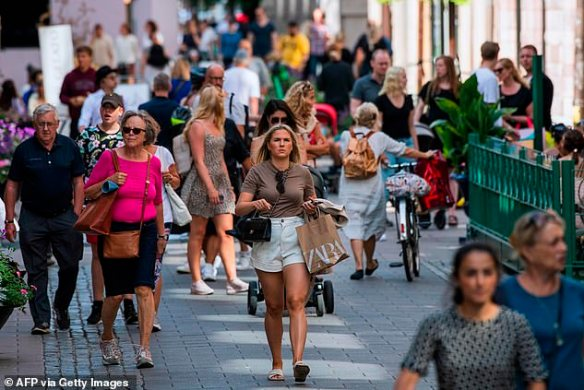 People walk along a street in Stockholm on Monday with nobody wearing masks, as continues to be normal in the Scandinavian nations