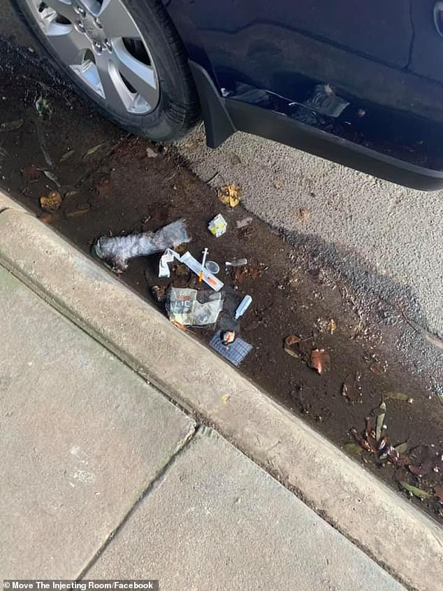 A needle and other paraphernalia is pictured in the gutter after being left by a drug user