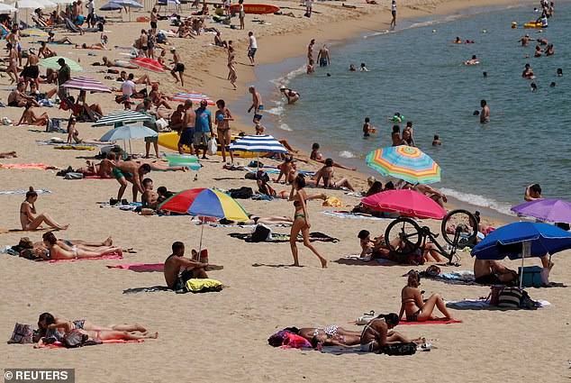 People are cooling off on a Barcelona beach yesterday.  Britain now advises against non-essential travel to Spain and its islands