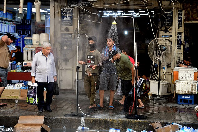 Iraqi men cool off in outdoor showers in Baghdad as temperatures rise to almost 125F (52C)