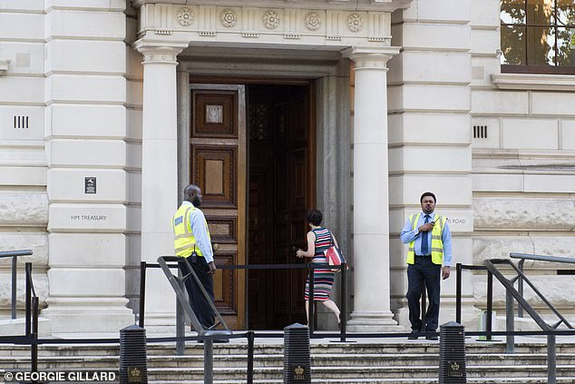 Ministerial departments in Whitehall are said to be 'ghost towns' with some seeing just 2 per cent of staff arriving at work this week. Pictured: A woman arrives at HM Treasury