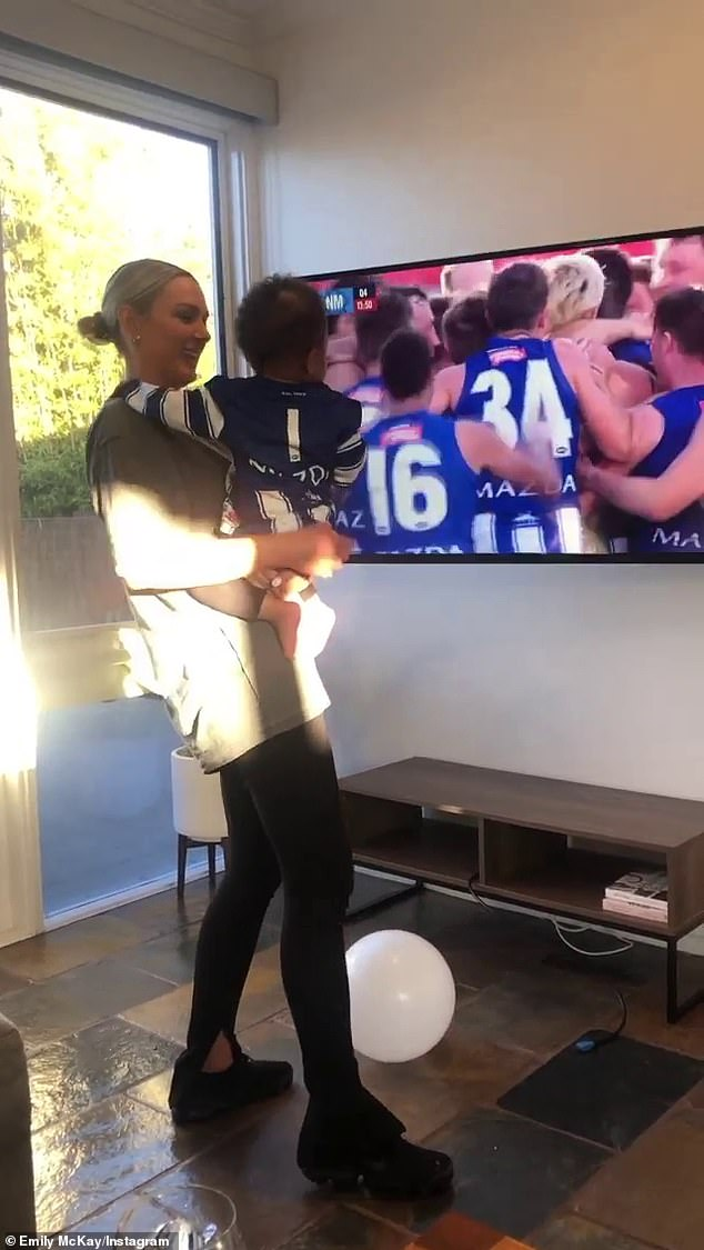 Daw's partner Emily McKay was holding their son Hendrix as they watched the game between North Melbourne and Adelaide Football Club on Saturday