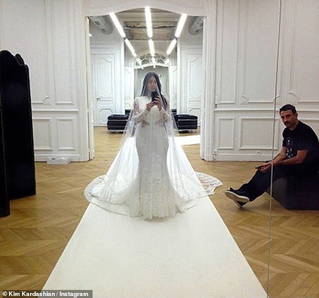Sensation: Kim could be glimpsed taking a full-length mirror selfie in her wedding dress as Riccardo, now creative director of Burberry, stood by