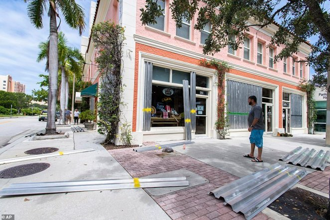 Bonnie Gruner's employees help board up the building she manages at in downtown West Palm Beach, Florida on Saturday