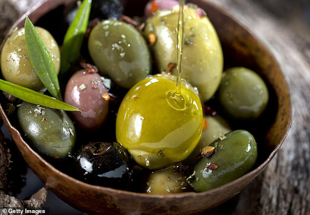 Some scientists believe the healthy fats abundant in the Mediterranean diet, found in nuts, fish, olive oil and some meat, may reduce the inflammatory molecules in the brain (file photo)