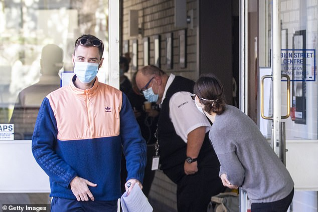 NSW residents are being recommended to wear face masks in public as coronavirus case numbers continue to rise. Pictured: three people leave the Albion Park coronavirus testing facility in Surry Hills
