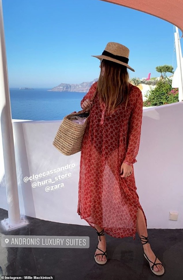 Working it: The media personality teamed her designer garment with a sheer red kaftan, lace-up sandals and a straw trilby hat as she stood by her five-star hotel Andronis Luxury Suites