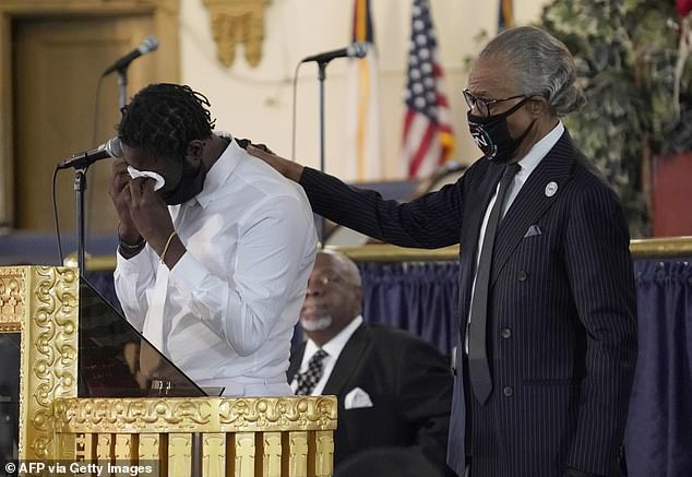 Al Sharpton comforts Davell Gardner Sr, father of the one-year-old boy shot and killed July 12