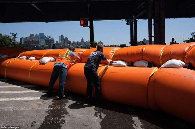Photos showed workers preparing a hydro-dam in the lower Manhattan area to prevent storm surge from Isaias