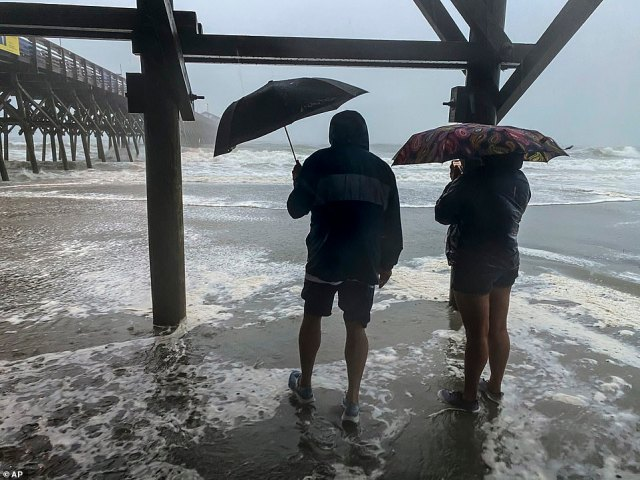 People walk at the Garden City Pier in Garden City, South Carolina, on Monday just hours before Isaias made landfall
