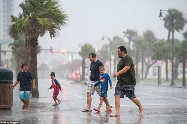 People walk across Ocean Boulevard in the rain in Myrtle Beach, South Carolina, on Monday afternoon