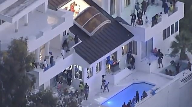 Footage from earlier last night showed hundreds of people packed across the stunning balconies of the Mulholland Drive villa as one reveler appeared to 'make it rain' - throwing dollar bills into the air, which showered into the pool below