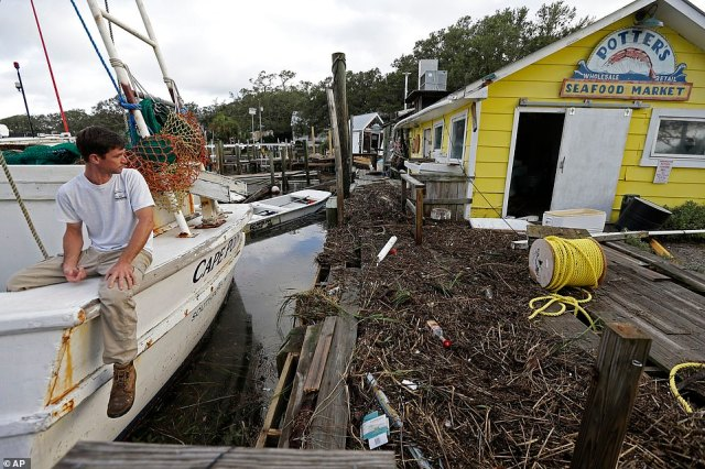 Royce Potter, a fifth generation seafood fisherman, surveys the damage to his business, Potter's Seafood Market, after Hurricane Isaias hit Southport, NC, overnight