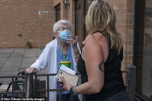 New Hampshire had the most nursing homes lacking PPE at about half without one week's supply of N95 masks, surgical masks and gowns, Pictured: Kay Foley, 88 (left) and her daughter Chris Coverdale blow kisses to each other after an outdoor visit at Jones-Harrison nursing home in Minneapolis, Minnesota, July 20