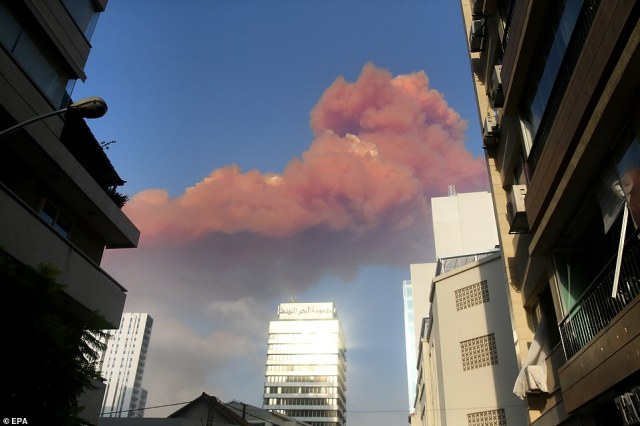 The thick plume of smoke looms over the city of Beirut on Tuesday evening after the explosion at the port