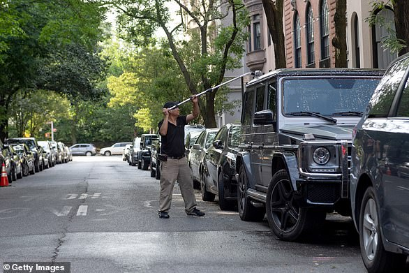 A man washes a Mercedes G- Class on a deserted street on Manhattan's Upper East Side. Many of New York City's wealthiest residents left the city in March and have not returned