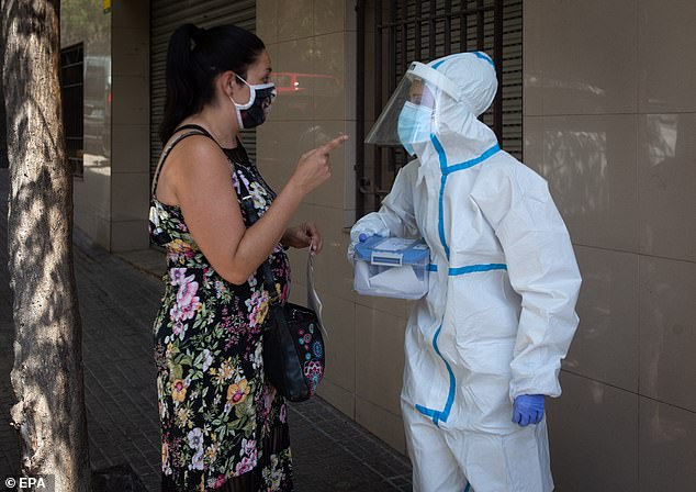 A woman asks a health worker about the voluntary testing for covid-19 that is taking place in Ripollet, Barcelona, Spain, 05 August 2020