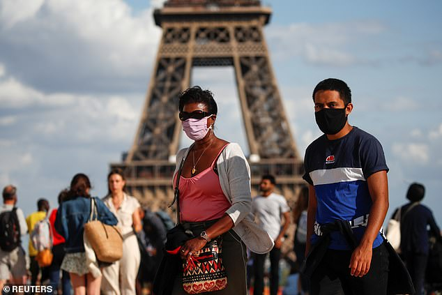 People wearing protective face masks walk at the Trocadero square near the Eiffel Tower in Paris as France reinforces mask-wearing as part of efforts to curb a resurgence of the coronavirus disease (COVID-19) across the country, August 3, 2020