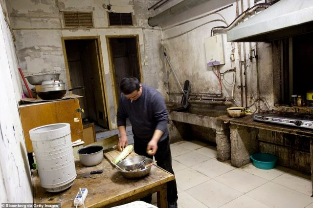 A man prepares food in the shared kitchen at a housing complex inside a Chinese bunker. The underground city, dubbed 'The Dungeon', was constructed in 1969 when the threat of nuclear war was at its peak