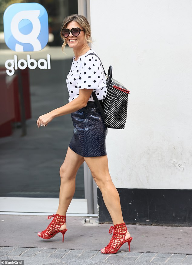 Legs for days:The TV and radio presenter, 37, put on a very leggy display in a black leather mini skirt and red caged heels as she made a stylish arrival