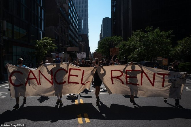New Yorkers carry a huge 'Cancel rent' banner as they march through the streets of New York Wednesday