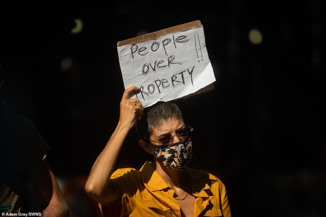 One woman holds up a sign reading 'People over poverty' as calls mount for rent to be canceled in New York