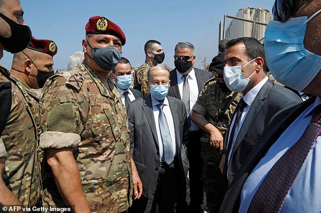 Lebanon's President Michel Aoun (centre)visits the site of a massive explosion the previous day in the heart of the Beirut
